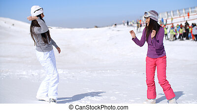 Two young women having a snow fight throwing snowballs as...