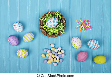 Easter eggs, basket, and candy on a blue background