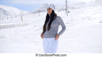 Attractive young woman standing in winter snow at a mountain...