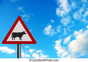 Photo realistic metallic reflective \'cattle\' sign, against a bright blue sky. With space for your text overlay / editorial