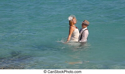 Groom holding bride in his arms by the sea - Groom holding...