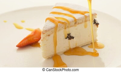 Slice of cheesecake with pouring sauce on plate on white table