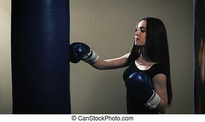 Attractive Female Punching A Bag With Boxing Gloves On...