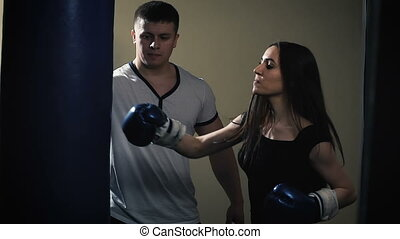 Cute brunette woman training with boxing gloves at the gym...