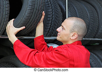 Tire Workshop - A mechanist working hard in a tire workshop