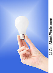Intuition - Human hands holding a bulb in front of a bright...