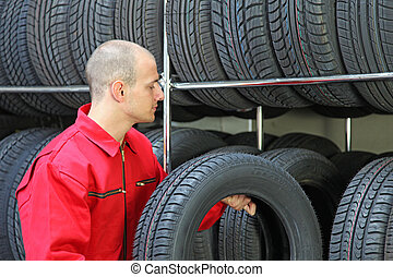 Working Mechanic - A working mechanic in a garage standing...