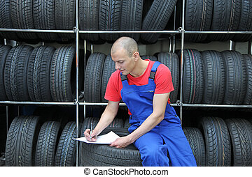 Stocktaking - A worker takes inventory in a tire workshop...