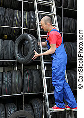 Restocking Tires - A motivated worker in a tire workshop...