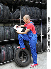 Checking The Stock - A worker takes inventory in a tire...