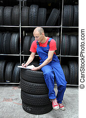 Working In A Tire Workshop - A worker takes inventory in a...