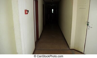 Man in cap backpack walk out dark corridor go down wooden stairs inside building