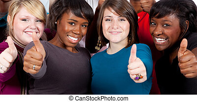 Multi-racial college students holding their thumbs up - A...