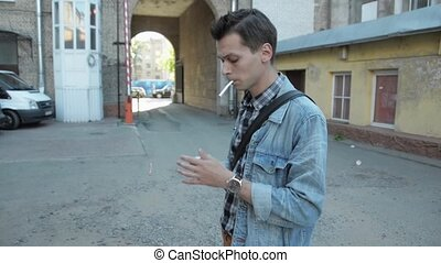Young man in jeans jacket light a cigarette by lighter....