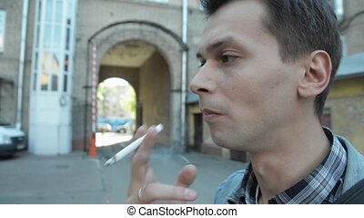 Face of young man smoking a cigarette focus in. Street....
