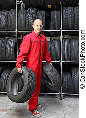 Tire Garage - A motivated worker in a tire workshop carrying...