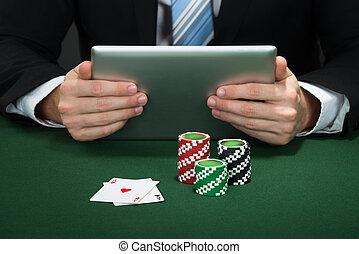 Poker Hand Holding Digital Tablet