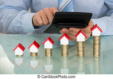 Businessman With Calculator In Front Of Coins And House...