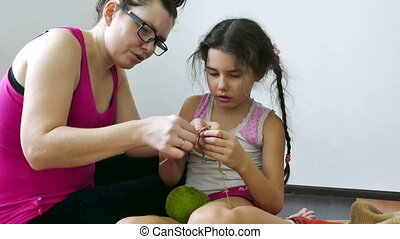 Mother and daughter knitting - woman and teen girl knitting...