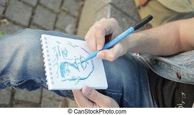 Man hands paint face by blue marker on paper notebook Summer...