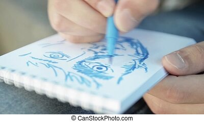 Man hands paint face by blue marker on paper notebook focus...