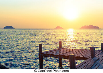 Wooden walkway on the sea coast during sunset
