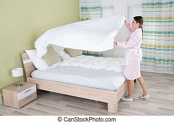 Female Housekeeper Changing Bedsheet On Bed - Young Female...