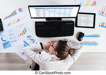 Businesswoman With Graphs Sleeping At Desk - Young...
