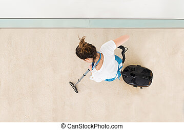 Young Female Janitor Vacuuming Floor - Young Female Janitor...