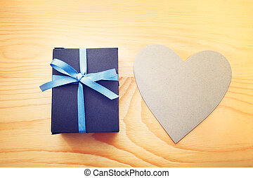 Giftbox and hand cut heart on wooden table - Present box and...