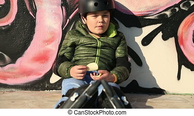 Young skater eating chips - Child with roller skate and...