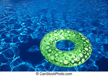 Open-air swimming pool - An inflatable green plastic ring...