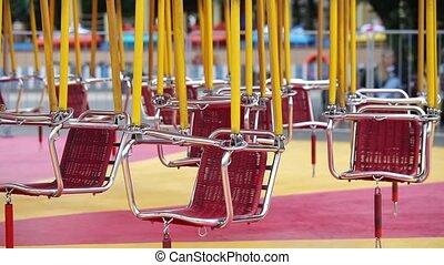 Empty carousel swings in amusement park
