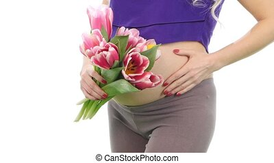 Pregnant woman holding her belly and bouquet of tulips, white, closeup