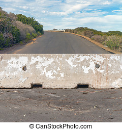 Concrete barrier blocking the uphill road - Rough texture...
