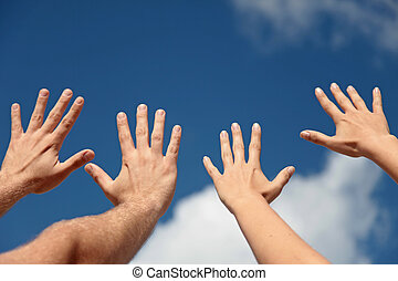 Hands up in the air - Two persons lifting their hands up in...