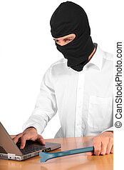 Cybercrime - A masked man using a notebook computer All...