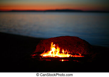Campfire by a lake at sunset