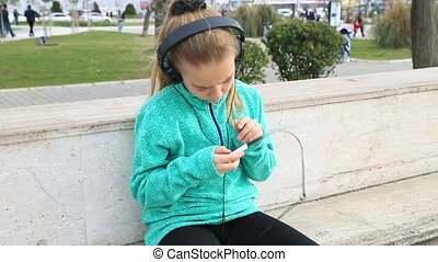 Young girl with headphones - Happy cute schoolgirl in park...