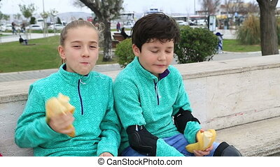 Young skaters eating banana - Portrait of a cute young boy...
