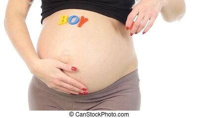 Color word baby near the pregnant tummy, white, closeup -...
