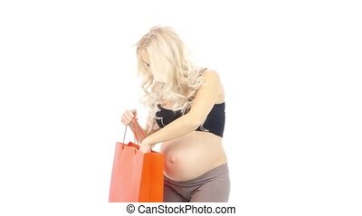 Pregnant woman gets out of the bag blue baby booties up to her belly waiting for baby, white