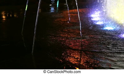 Colored water fountain at night. water running texture with...