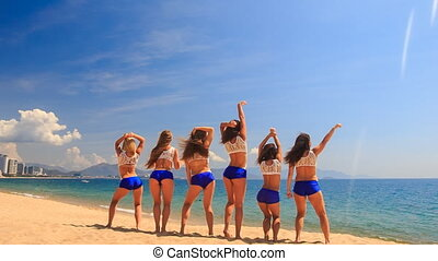 cheerleaders from backside perform Basket Toss on sand -...