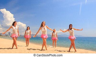 cheerleaders dance bend in poses on beach against sea