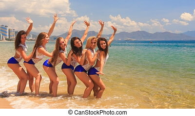 cheerleaders stand in shallow water wave hands send kisses -...