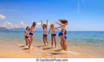 cheerleaders in white blue jump run along shallow water