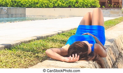 girl in blue lies bends legs on stone barrier against pool