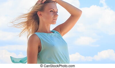 blonde girl in transparent smoothes hair under wind on beach...