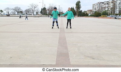 Young skaters skating to  camera